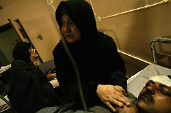 Baija Khader comforts her son Falah Hassan, 35, a would-be recruit for the Iraqi Army, at Al Karah hospital, Baghdad, Iraq Feb. 11, 2004. A suicide attacker detonated a car packed with explosives in a crowd of hundreds of Iraqis waiting outside a Baghdad army recruiting center Wednesday, killing up to 46 people in the second bombing in two days targeting Iraqis working with the U.S.-led coalition. The attack backed threats that insurgents would step up violence to disrupt the planned June 30 handover of power to the Iraqis.