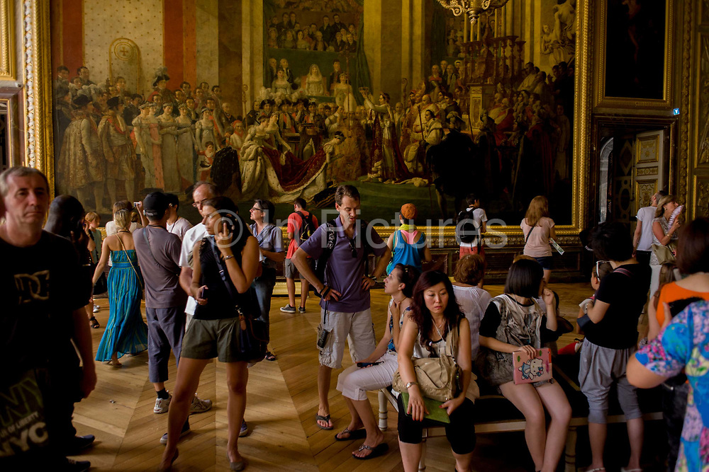 Tourists admire the Coronation of Napoleon in Coronation room of the King's apartments in the Palace of Versaille, near Paris. The painting (Le Sacre de Napoléon) is a work of almost 10 x 6 metres completed in 1807 by Jacques-Louis David, the official painter of Napoleon. The crowning and the coronation took place at Notre-Dame de Paris, a way for Napoleon to make it clear that he was a son of the Revolution. The Palace of Versailles or simply Versailles, is a royal château in Versailles in the Île-de-France region of France. In French it is the Château de Versailles.