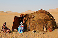 Himba woman with child and old woman sitting by a mud hut in Namibia, Africa. Fine art photography print.<br />