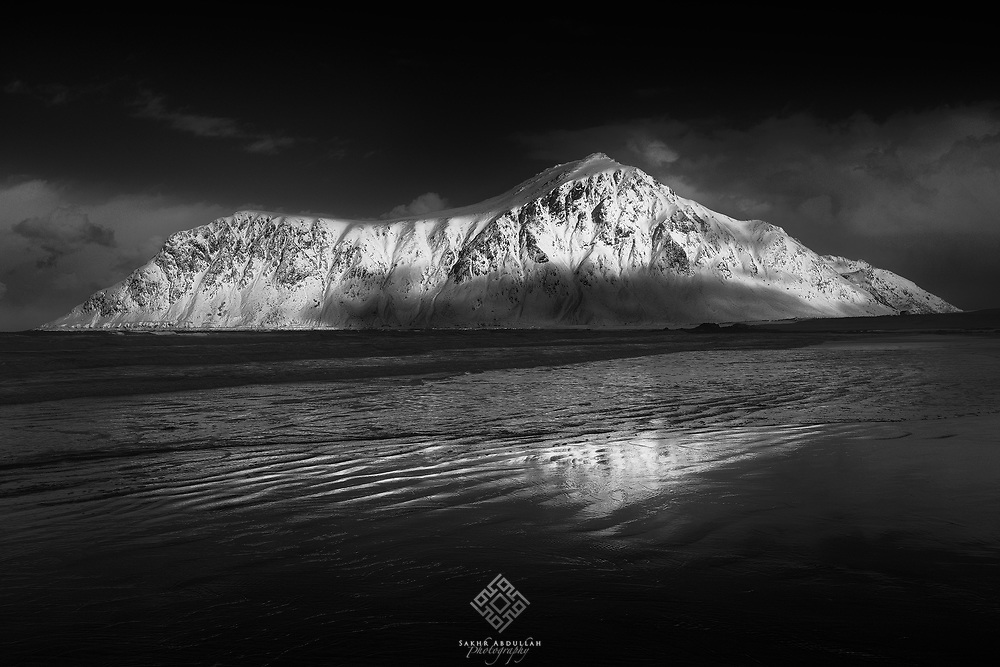 Skagsanden is a popular beach on the Lofoten Islands. It's most known for its fascinating black-sand patterns and at times perfect reflections of the picturesque mountain in the background.<br /> <br /> After a stormy cold night, I was lucky that morning when everything was under the shadow of clouds except that beautiful mountain which wears snow and light!