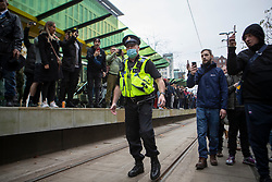 © Licensed to London News Pictures. 08/11/2020. Manchester, UK. A lone police officer is surrounded by protestors as thousands attend anti-lockdown protest in Manchester. Photo credit: Kerry Elsworth/LNP