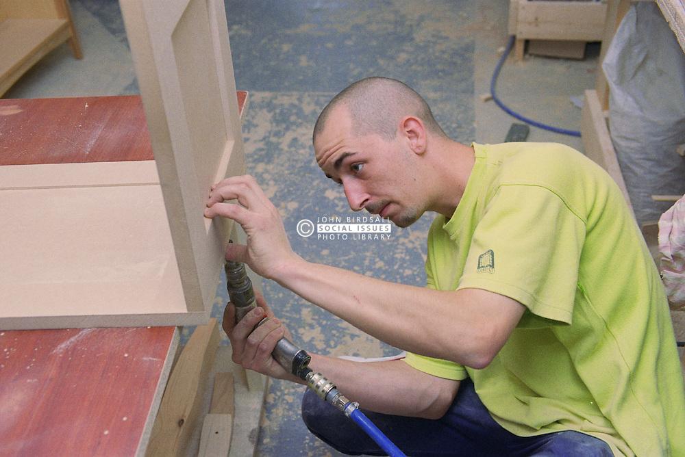Cabinet maker assembling blanket box using drill,