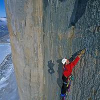 BAFFIN ISLAND, NUNAVUT, CANADA. Photographer's shadow leaps over Alex Lowe, aid climbing high on Great Sail Peak. Stewart Valley below.