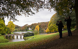 © Licensed to London News Pictures. 05/11/2016. Stourton, UK.  A couple taking photographs of the autumn colours at Stourhead Gardens in Wiltshire today, 5th November 2016.  Photo credit: Rob Arnold/LNP