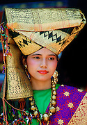Local young girl wearing traditional ornate gold head-dress with gold necklace and earrings  in Java, Indonesia.