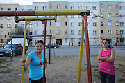 19 year old Isabella Baboi  and her sister Corinna in the children's playground outside her home in Alexandria, where she lives with her mother and sister. She was expelled from France on 25th September by the police authorities for stealing chewing gum and face-cream. She declared herself as being homeless and returned to Romania with just the clothes she was wearing at the time of her arrest. She will return to Paris suburbs very soon, where her father and cousins are living. Alexandria, Romania..Roma Gypsies left India 1000 years ago. Often nomadic. A collection of tribes with their own languages and culture, pushed by the Ottoman empire towards Europe, used and sold as mercenaries, slaves, prostitutes. They endured 500 years of slavery until mid 19th century. A million were killed in the holocaust. Hundreds of thousands exiled and refugees from kosovo. Many Eastern Europe Roma come to the west seeking a better life. They are shunned, marginalized, excluded. Both indigenous and foriegn Roma, whether European citizens or not, lack the opportunities of others, living on the periphery, in the brunt of racism, often deported back to their countries of origin.