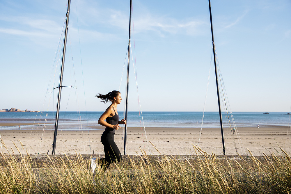 Lady jogging along the waterfront with the view of the beach neyond in St Aubin. Jersey, Channel Islands