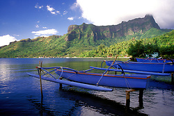 """Cook's Bay, Moorea.  From Wikipedia:  Moorea is a high island in French Polynesia, part of the Society Islands, 17 km (roughly 9mi) northwest of Tahiti. Its position is 17°32?S, 149°50?W...Several ferries go to the Vaiare wharf in Moorea daily from Papeete, the Tahitian capital. Moorea's Temae Airport (MOZ) has connections to the international airport in Papeete and onward to other Society Islands...The island is administratively part of the commune (municipality) of Moorea-Maiao, itself in the administrative subdivision of the Windward Islands...Because of its stunning scenery and accessibility to Papeete, Moorea is visited by many western tourists who travel to French Polynesia. Especially popular as a honeymoon destination, Moorea can often be seen in advertisements in American wedding magazines...From above, the shape of the island vaguely resembles a fork, with its two nearly symmetrical bays opening to the north side of the island: Cook's (or Paopao) Bay and Oponohu Bay. The island was formed as a volcano 1.5 to 2.5 million years ago, the result of a geologic hotspot in the mantle under the oceanic plate that formed the whole of the Society Archipelago. It is theorized that the current bays were formerly river basins that filled during the Holocene searise...Charles Darwin was inspired for his theory regarding the formation of coral atolls when looking down upon Moorea standing on a peak on Tahiti. He described it as a """"picture in a frame,"""" referring to the barrier reef encircling the island..."""