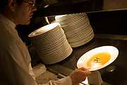 "Using a cloth, a waiter picks up a hot bowl of Butter Squash soup ready for a la carte service in the kitchens at the Vivre restaurant in Sofitel, a 605 bedroom, 27 suite and 45 meeting room accommodation and business hub Heathrow Airport's hub hotel attached to Terminal 5. A stack of clean and unused plates are ready for use on the hot plate that warms them  and we see the waiter leaning over in shadow, carefully taking hold of the bowl so that none of the liquid spills. The man is wearing a smart white shirt and is about to take the dish over to the customer's table. From writer Alain de Botton's book project ""A Week at the Airport: A Heathrow Diary"" (2009)."