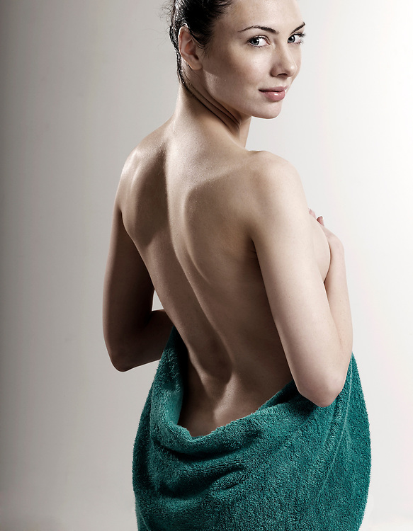 Back view of a nude woman holding a green towel around her torso and hips after a bath