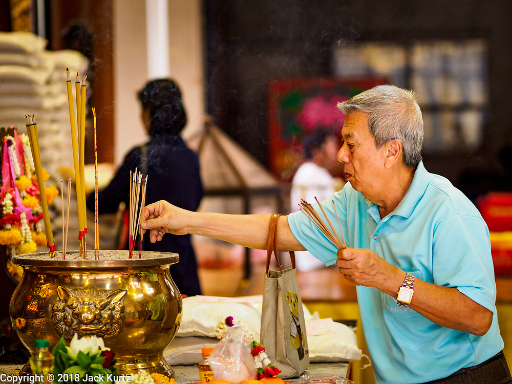 31 JULY 2018 - BANGKOK, THAILAND: A man lights incense at Wat Mangkon Kamalawat in Chinatown. Bangkok's Chinatown district is one of the largest Chinatowns in the world. It was established in 1781 when Siamese King Rama I gave the Chinese community in Bangkok land outside of Bangkok's city walls so he could build his palace (what is now known as the Grand Palace). Chinatown is now the heart of the Thai-Chinese community. About 14% of Thais have Chinese ancestry.    PHOTO BY JACK KURTZ