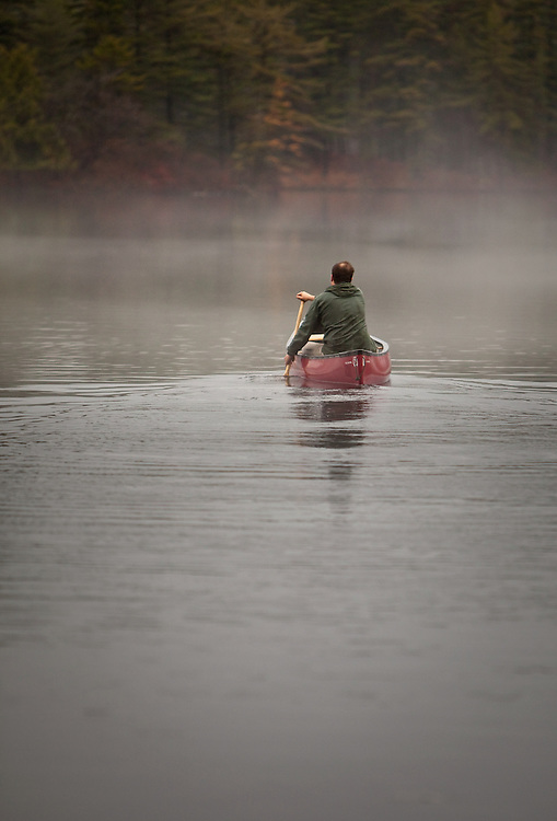 Man paddling a canoe on through fog on a quiet Adirondack pond, New York.