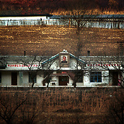 Near Hoeryong town, North Korea, 11-2003..A North Korean school bearing the portrait of deceased leader Kim Il Sung. ..Installed by the Soviets in 1948, Kim Il Sung maintained an iron-grip on the nation through a system of indoctrination, purges and terror. When the Great Leader died in 1994, his son?s succession rested on a divine right. . .North Korea is the world's most insular and totalitarian state. Ruled by the messianic leader Kim Il Sung and his son Kim Jong Il since 1948, North Korea has stubbornly stuck to its juche (self-reliance) ideology and siege mentality, imposing one Stalinist economic plan after another. Floods, droughts and mismanagement in the 1990s plunged the country into a preventable famine, killing up to three million, or 13 percent of the population. It now depends heavily on Chinese aid...