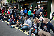 Young people eating McDonalds fast food on the street. Sitting on a kerb outside the restaurant this group of students all sit in a row having their lunch. London, UK.