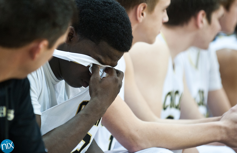 Concord senior Xavier Stywall covers his face as the Spiders lost to Hickory in the regional round of the NCHSAA 3A playoffs Thursday night at the University of North Carolina at Greensboro. Hickory won the game 95-82 to end the Spiders season. (Photo by James Nix)