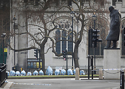 © Licensed to London News Pictures.23/03/2017.London, UK. A statue of Winston Churchill looks down on Parliament Square as police officers in protective suits conduct a fingertip search. Yesterday a lone terrorist killed 4 people and injured several more, in an attack using a car and a knife at Parliament and on Westminster Bridge. The attacker managed to gain entry to the grounds of the Houses of Parliament, killing one police officer.Photo credit: Peter Macdiarmid/LNP