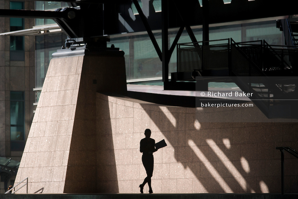 Silhouette of woman walking through the Broadgate corporate offices development in the City of London. Carrying some paperwork or files, the lady walks under steel structure with the backdrop of the Broadgate development within the ancient boundary of the capital's Square Mile, it's financial district founded by the Romans in AD43.