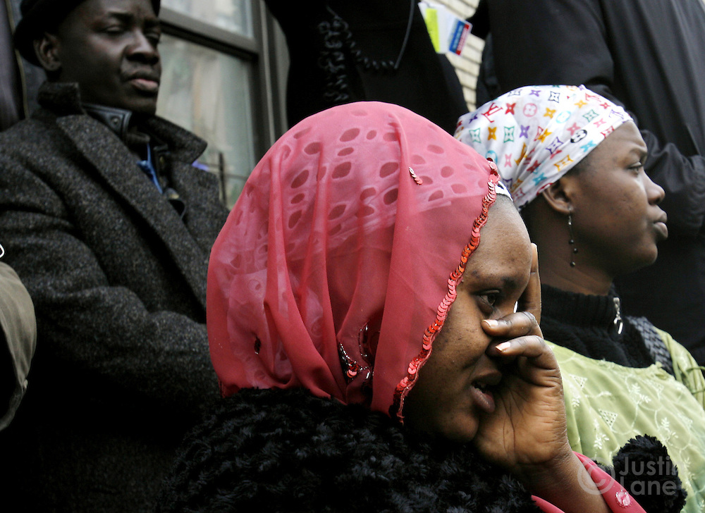 A woman covers her face while watching the funeral service for the ten people killed in a recent house fire at the Islamic Cultural Center in the Bronx, New York on Monday 12 March 2007. Of the ten people killed in the fire, 9 were children, and all were immigrants from Mali.
