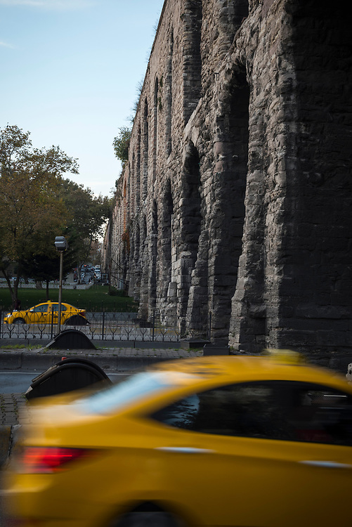 Taxis drive through arches at Valens Aqueduct on Atatürk Boulevard in Istanbul, Turkey. Built in the late 4th century AD by Roman Emperor Valens, it was maintained and used by the Byzantines and later the Ottomans.