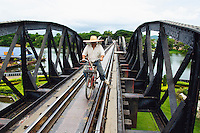 Man rides bike across the bridge over the river Kwai, Death Railway, Kanchanaburi, Thailand