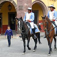 North America, Mexico, San Miguel de Allende.  Horseback caballeros ride through the center of town in San Miguel de Allende.