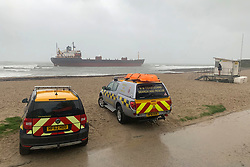 © Licensed to London News Pictures. 18/12/2018. Falmouth, UK. Search and rescue teams watch Russian cargo ship Kuzuma Minin which has run aground on the reef off Gyllyngvase beach in Falmouth Bay in the early hours this morning. The Falmouth lifeboat and the Coastguard helicopter are involved in the major incident.  Photo credit: Mark Hemsworth/LNP