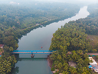 Aerial view of Sadolxem bridge over Talpon river with a boat in Canacona , South Goa, India.