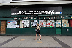 © Licensed to London News Pictures. 19/06/2015. London, UK. A woman walks past the occupation signs in the window at the Elephant and Castle pub in Southwark, south-east London. A group of activists have occupied the Elephant and Castle pub and are squatting in it to prevent Foxtons Estate Agents from opening an Estate Agent branch. The activists, who are against gentrification want the historic pub site to become a community asset with open use. The Elephant and Castle pub closed earlier this year after its license was revoke and in April, representatives of Foxtons notified planning authorities that they intend to open a branch of the estate agents chain in the pub. Photo credit : Vickie Flores/LNP