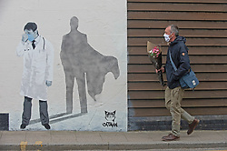 © Licensed to London News Pictures 28/04/2021. Whitstable, UK. A man walking past a Catman mural of an NHS superhero doctor. People in Whitstable High Street in Kent wearing masks to protective themselves against the threat of Coronavirus. Photo credit:Grant Falvey/LNP