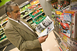 Older man looking at a magazine in a shop,