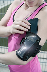 Young woman putting mobile phone in her arm band, Bavaria, Germany