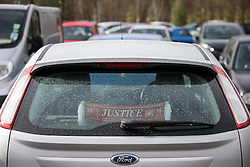 """© Licensed to London News Pictures . 12/02/2016 . Warrington , UK . A Hillsborough """" JUSTICE """" scarf hung in the rear windscreen of a car parked outside the Hillsborough Inquest at Birchwood Park in Warrington today (12th February 2016) . Photo credit : Joel Goodman/LNP"""