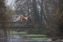 Denham, UK. 7th December, 2020. An excavator is driven across a bridge in Denham Country Park during works for the building of a bridge in connection with the HS2 high-speed rail link. Anti-HS2 activists continue to resist the controversial £106bn rail project from a series of protest camps based along its initial route between London and Birmingham.