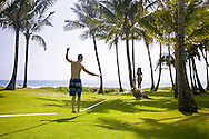 A young couple slacklining between palm trees in Poipu, Kauai.