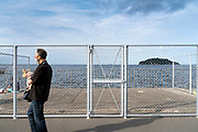 man walking with dog at Umikaze park, Yokosuka with Tokyo Bay and Sarushima Island