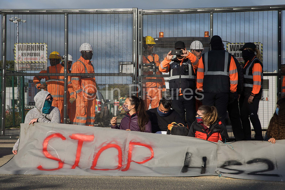 Environmental activists from HS2 Rebellion sit in the road behind a banner to block a gate providing access to a site for the HS2 high-speed rail link on 12 September 2020 in Harefield, United Kingdom. Anti-HS2 activists continue to try to prevent or delay works on the controversial £106bn HS2 high-speed rail link in the Colne Valley where thousands of trees have already been felled.