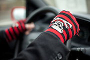 """A man is driving his car with """"skull and bones"""" gloves."""