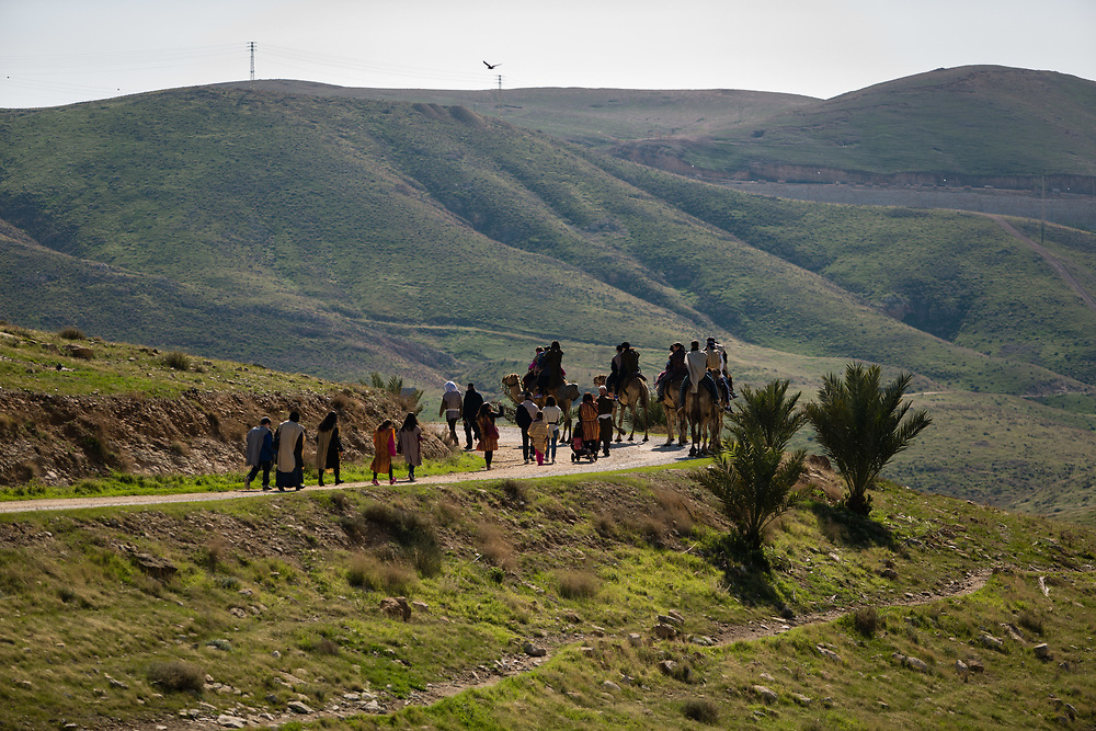 Tourists ride camels along the ridge above the riverbed of Wadi Qelt (Nahal Prat in Hebrew) dressed in biblical style clothes, as they take part in the 'Genesis Land Experience' at the West Bank Jewish settlement of Alon, on January 28, 2016.