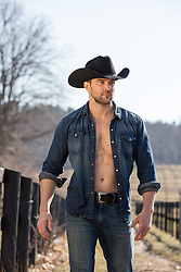 hot cowboy with an open shirt outdoors in the sun