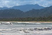 Surfers in the waves, Red Island Beach, Red Island, Banyuwangi Regency, East Java, Indonesia, Southeast Asia