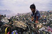 Asia, Philippines, Manilla, Smokey Mountain Rubbish dump. Children sifting throguh the rubbish. Thousands of poor and often indigenous people work sifting through the rubbish, recycling materials such as paper, various metal and plastic. They earn about $1 a day. The place is rife with disease. © Nigel Dickinson