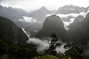 A view of the shrouded Andean mountains surrounding the ancient site of Machu Pichu in the Cusco region of Peru.