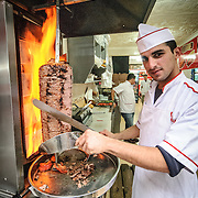 A cook carving slices of a grilling doner kebap in Istanbul, Turkey.