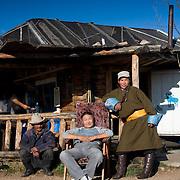 Local men relax outside simple wooden Mongolian cabin (Khangil Nuur, Mongolia - Sep. 2008) (Image ID: 080915-0826081a)