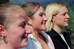 Profile of teenage girls standing together smiling,