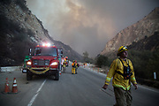 Firefighters close the road due to the 60 feet fire comes down from the smoke comes from Maricopa Highway. They saved five houses, and the owners of the house look for the smoke from behind the stop sign. On Thursday, December 7th, 2017 at Maricopa Highway in Ojai, California. (Photo by Yuki Iwamura)