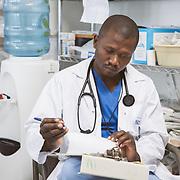 INDIVIDUAL(S) PHOTOGRAPHED: Dr. Etienne Aral. LOCATION: Sacré-Cœur Hospital, Milot Commune, Cap-Haïtien, Haïti. CAPTION: Dr. Etienne Aral writes notes in a patient's file at the emergency room of Sacré-Cœur Hospital.