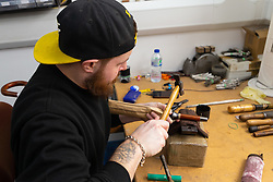 Umbrella maker Lee puts the finishing touches to an umbrella. Craftspeople at Fox Umbrellas Ltd, a company in Croydon, Surrey, that has been going for over 150 years hand build quality umbrellas. Croydon, Surrey, March 06 2019.
