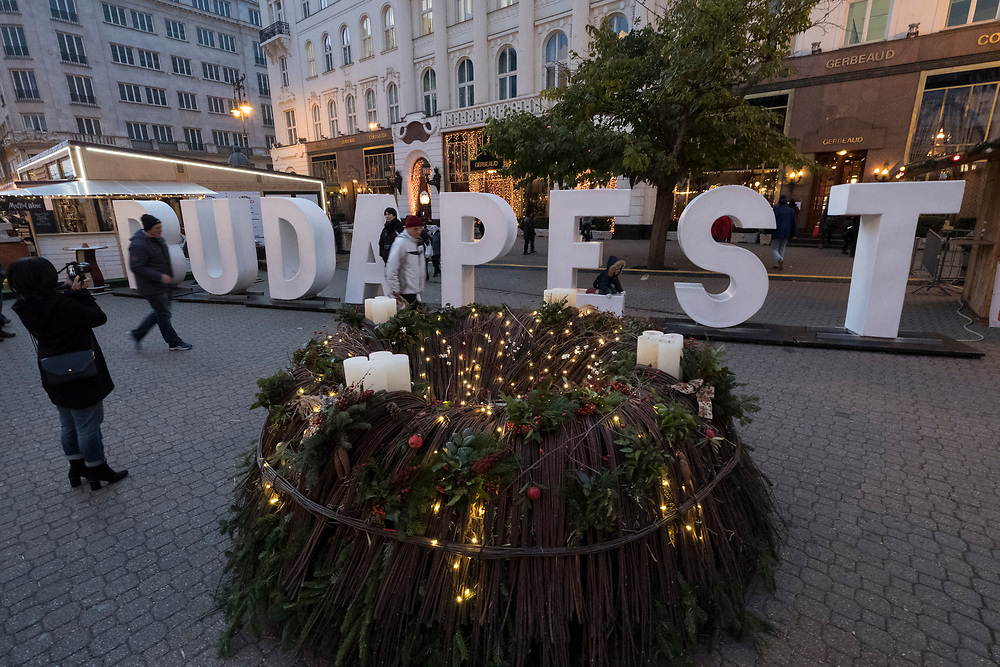 """BUDAPEST, HUNGARY - DECEMBER 07:  A woman takes a picture in front of the writing """"Budapest"""" in Vorosmarti Square on December 7, 2017 in Budapest, Hungary. The traditional Christmas market and lights will stay until 31st December 2017."""