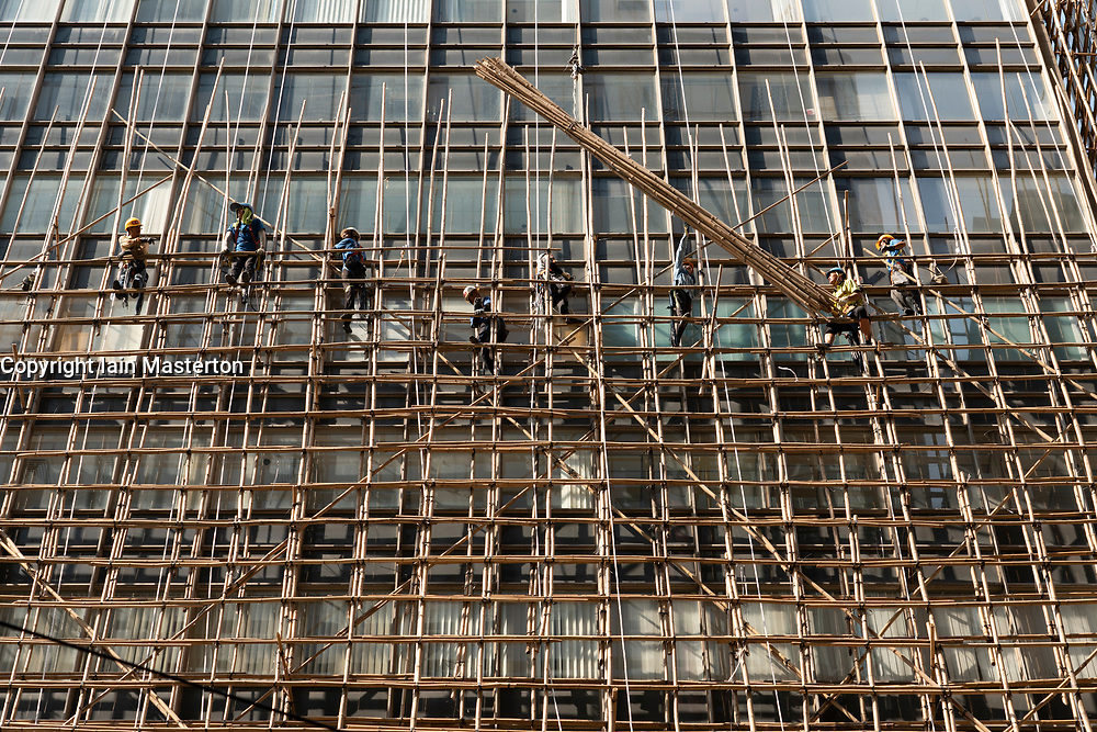 Central, Hong Kong. 2 October. Workers erect bamboo scaffolding up high-rise office tower. Bamboo is commonly used in Hong Kong because of its low cost and weight. Iain Masterton/Alamy Live News.